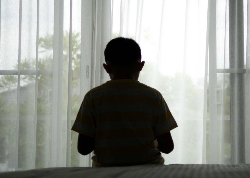 ילד עצוב יושב על מיטה